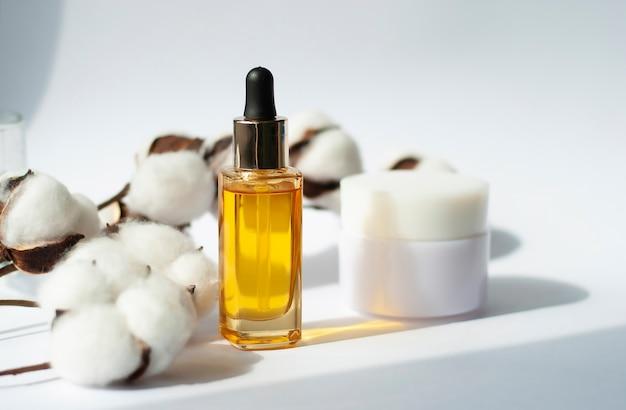 Frasco de óleo cosmético amarelo e creme com galho de algodão