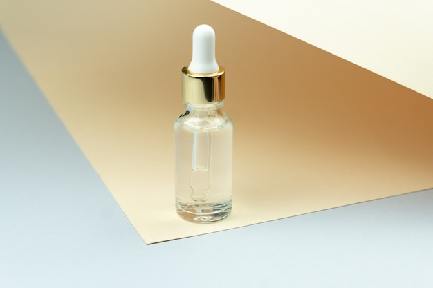 Frasco de óleo cosmético com conta-gotas pipeta em fundo bronzeado. conceito de cuidado de pele.