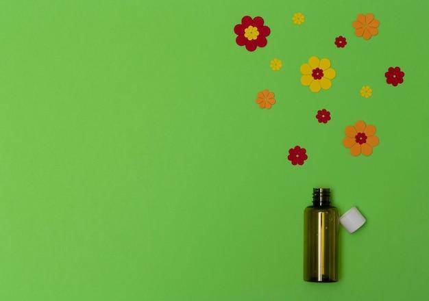 Frasco de óleo de flor e flores de papel brilhantes no conceito de medicina alternativa saudável de fundo verde