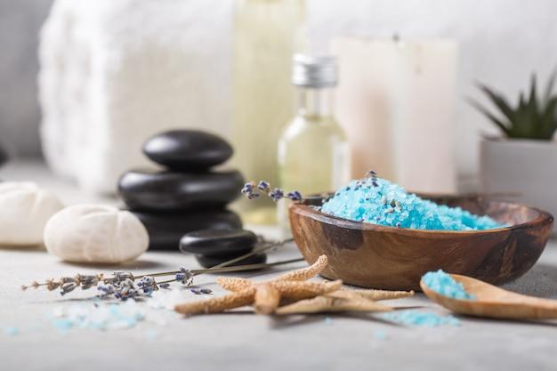 Frasco de óleo de massagem de aroma essencial e natural sal de fragrância com pedras, velas na mesa de concreto cinza.