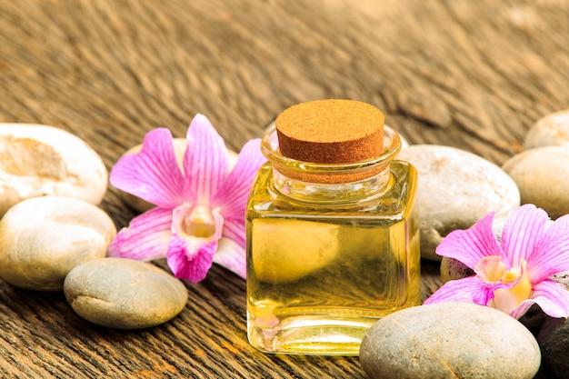 Frasco de óleo essencial de aroma ou spa com pedra zen na mesa de madeira
