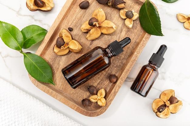 Frasco de óleo essencial de camélia e sementes de camélia na bandeja de madeira. beleza, cuidados com a pele, bem-estar