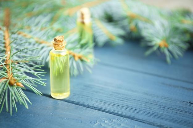 Frasco de óleo essencial de coníferas e galhos em superfície de madeira