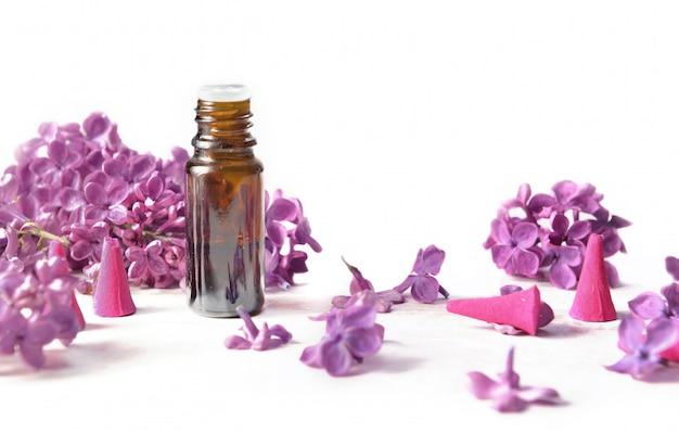 Frasco de óleo essencial e incenso entre pétalas de flores lilás em branco