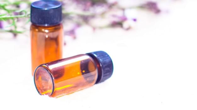 Frasco de óleo essencial. frasco conta-gotas de fitoterapia ou aromaterapia isolado no fundo branco. flores de alecrim frescas e óleos essenciais na mesa