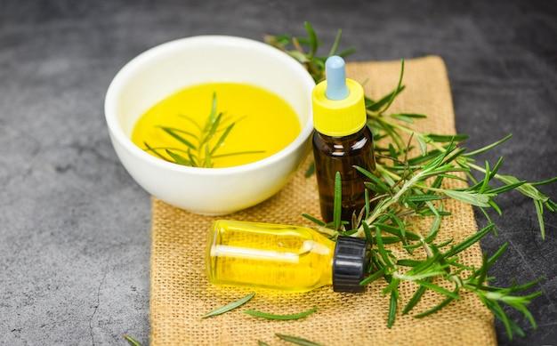 Frasco de óleo essencial spa natural ingredientes óleo de alecrim para aromaterapia e planta de folhas de alecrim no fundo do saco - cosméticos orgânicos com extratos de ervas