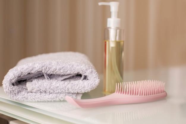Frasco de óleo micelar de limpeza e pente com toalha de banho em uma mesa sobre um fundo bege neutro. espaço para texto