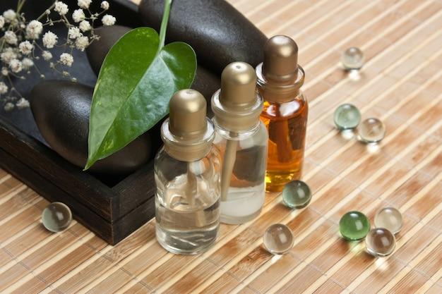 Frasco de óleos cosméticos com pedras de spa