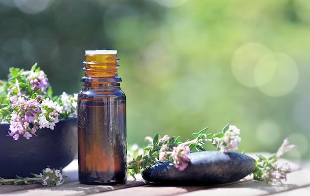 Frasco de óleos essenciais derramado sobre uma mesa com flores de lavanda em fundo verde bokeh