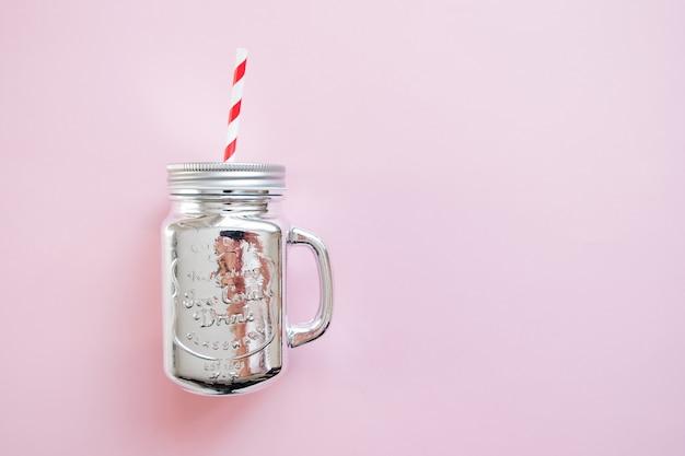 Frasco de pedreiro de prata do natal com palha no fundo cor-de-rosa. natal de inverno plano leigos