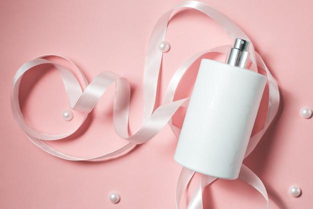 Frasco de perfume branco em fundo rosa
