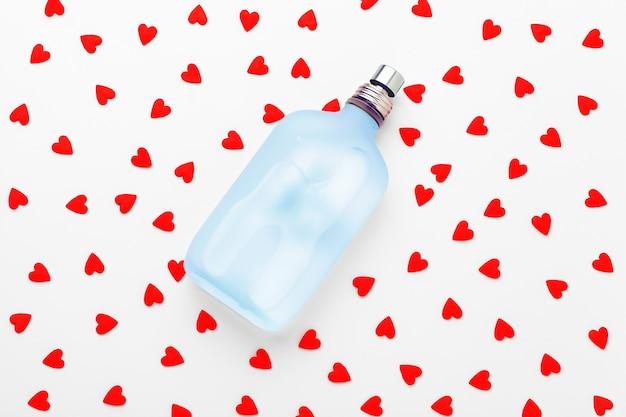 Frasco de perfume com corações vermelhos
