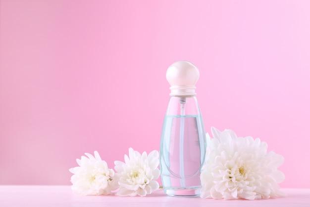 Frasco de perfume com flores brancas em rosa