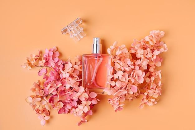 Frasco de perfume com flores cor de rosa em fundo pastel. conceito de beleza
