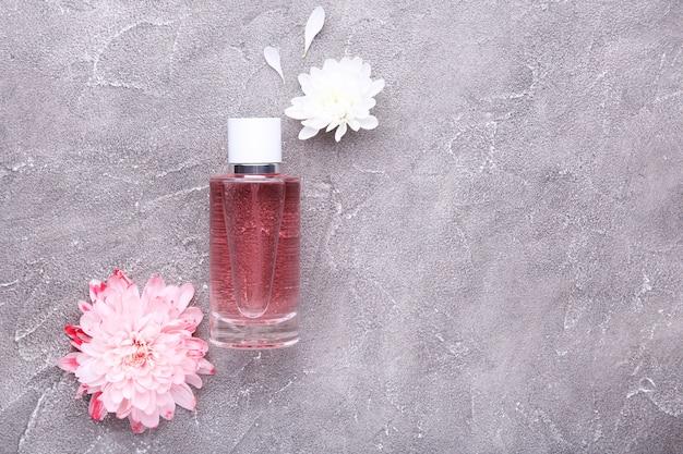 Frasco de perfume com flores em fundo cinza de concreto