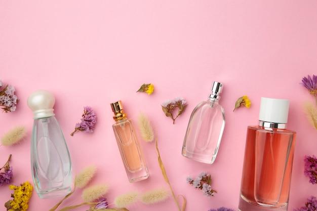 Frasco de perfume com flores na superfície rosa com espaço de cópia