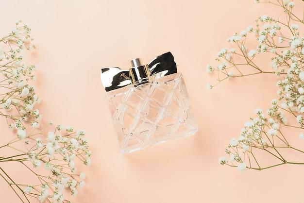 Frasco de perfume com flores secas em uma vista superior do plano de fundo bege