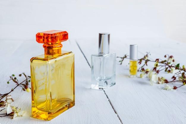 Frasco de perfume com flores sobre fundo branco de madeira