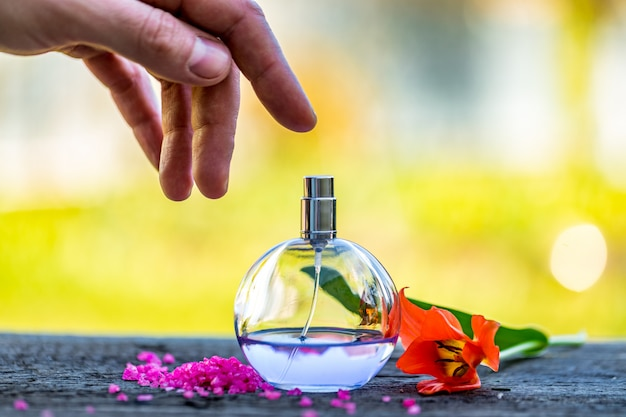 Frasco de perfume com flores sobre fundo claro