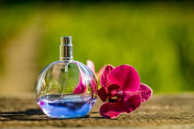 Frasco de perfume com flores sobre fundo de cor bokeh.