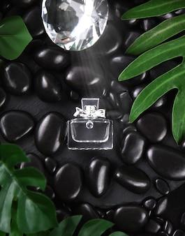 Frasco de perfume com folhas verdes frescas e pedra preta