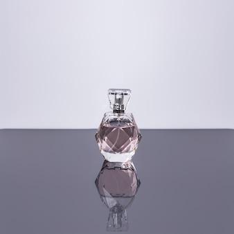 Frasco de perfume com reflexo na superfície branca