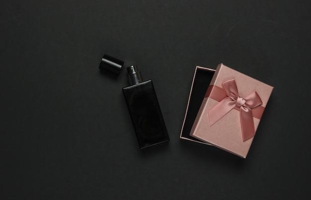 Frasco de perfume com uma caixa de presente em um fundo preto. vista do topo