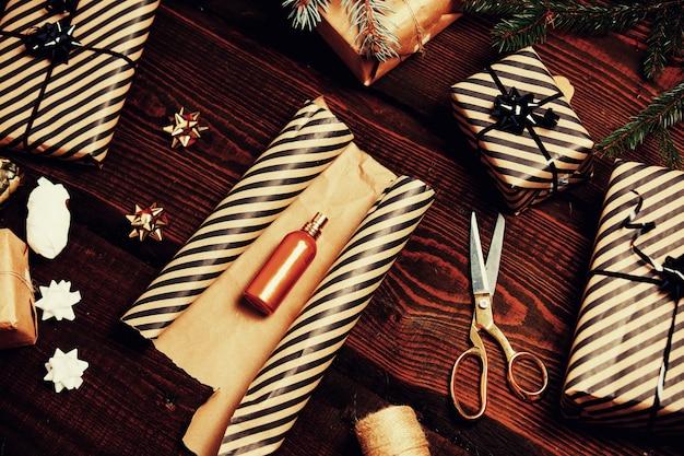 Frasco de perfume dourado com presentes de natal em torno de uma mesa