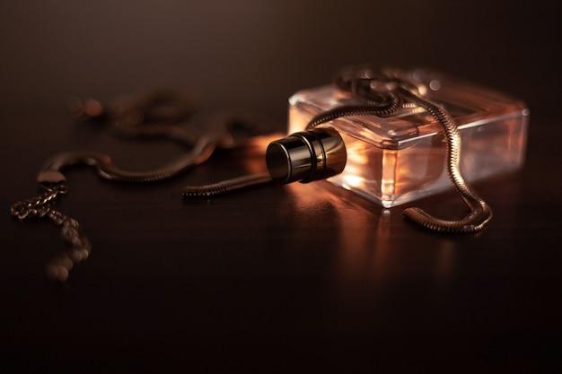 Frasco de perfume e acessórios em fundo escuro