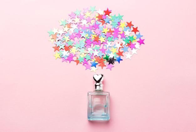 Frasco de perfume e confetes em fundo rosa, lay plana