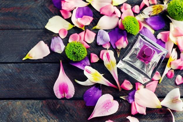 Frasco de perfume e pétalas de flores em madeira