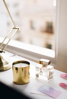 Frasco de perfume e uma vela perto de uma janela