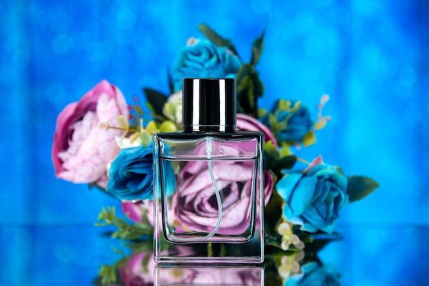 Frasco de perfume elegante com flores coloridas de frente para o fundo azul
