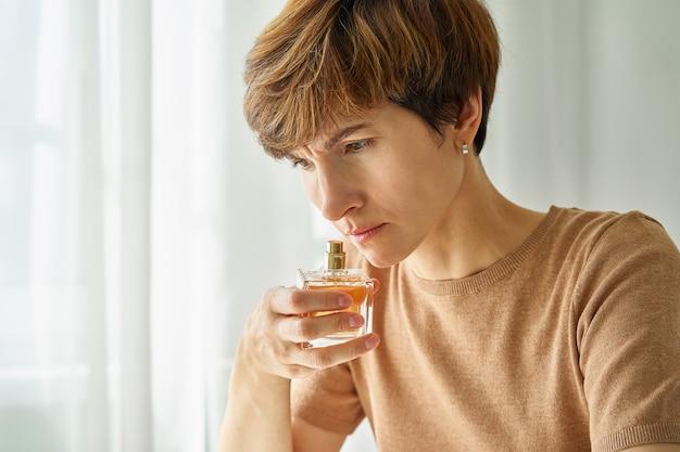 Frasco de perfume feminino cheirando e verificando a presença de sintoma cobiçoso de longa duração