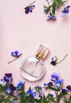 Frasco de perfume feminino e violetas flores sobre fundo rosa