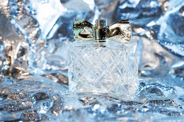 Frasco de perfume feminino elegante em luzes de néon na folha com superfície brilhante amassada