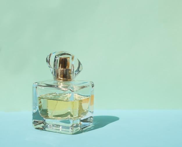 Frasco de perfume feminino em um fundo azul pastel com sombras de cristal