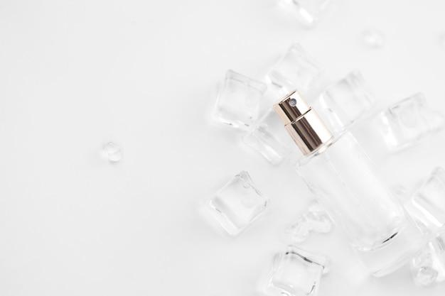 Frasco de perfume feminino, fotografia objetiva do frasco de perfume em cubos de gelo e água.