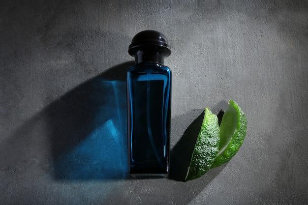 Frasco de perfume masculino moderno e fatias de limão no plano de fundo texturizado cinza