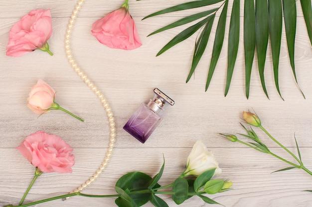 Frasco de perfume, miçangas em um cordão, flores brancas e rosa, folhas verdes sobre fundo de madeira. cosméticos woomen. vista do topo.