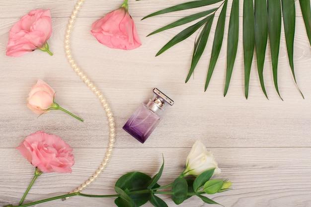 Frasco de perfume, miçangas em uma corda com flores brancas e rosa e folhas verdes em fundo de madeira. cosméticos woomen. vista do topo.