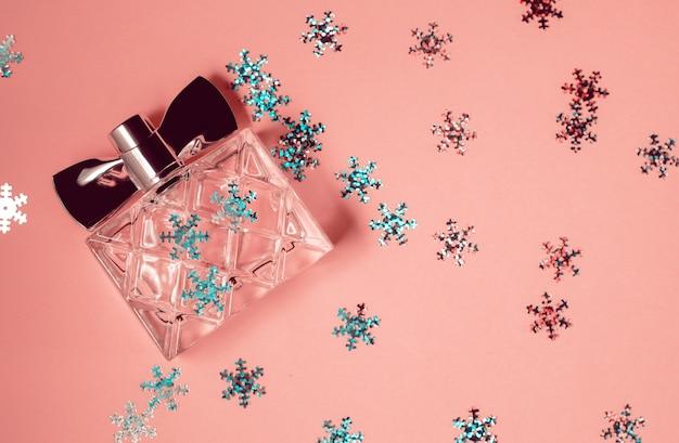 Frasco de perfume moderno em fundo rosa