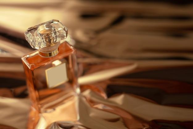 Frasco de perfume na superfície dourada
