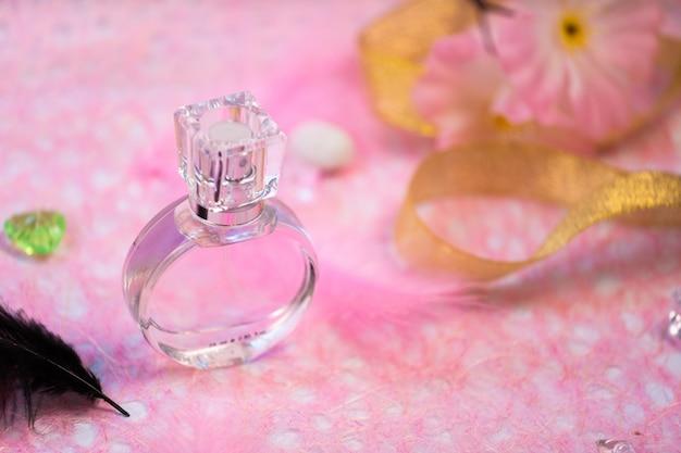 Frasco de perfume no fundo rosa