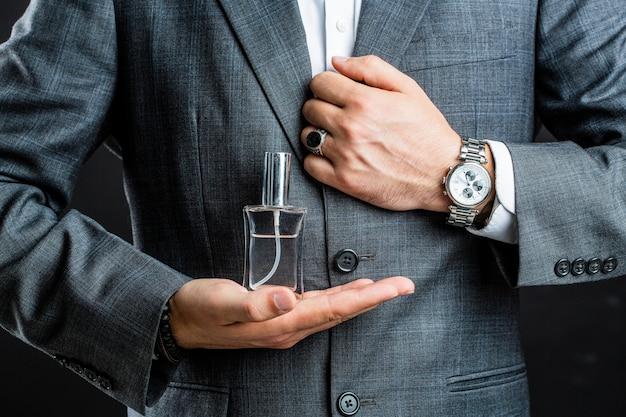 Frasco de perfume ou colônia e perfumaria, cosméticos, frasco de perfume de perfume, colônia masculina segurando.