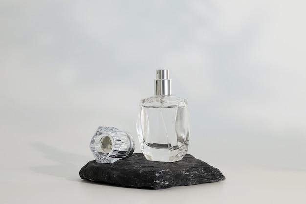 Frasco de perfume sem marca em pé no pódio de pedra. apresentação de perfume em fundo branco. brincar. conceito de tendência em materiais naturais. essência feminina e masculina. cosmético natural.