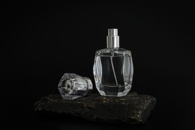 Frasco de perfume sem marca em pé no pódio de pedra. apresentação do perfume no fundo preto. brincar. conceito de tendência em materiais naturais. essência feminina e masculina. cosmético natural.
