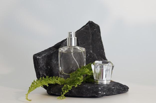 Frasco de perfume sem marca no pódio de pedra com plantas. apresentação de perfume em fundo branco. brincar. conceito de tendência em materiais naturais. essência feminina e masculina. cosmético natural.