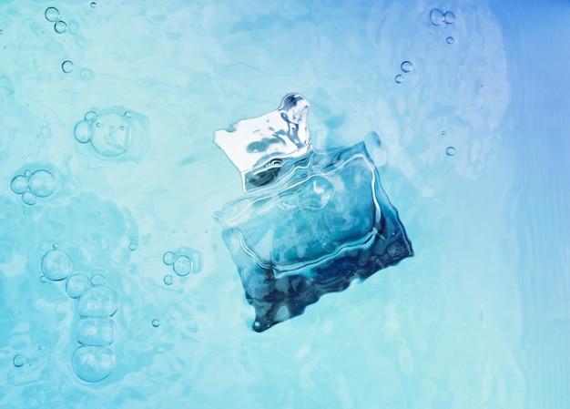 Frasco de perfume transparente azul debaixo d'água, ondas acima dele.