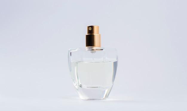 Frasco de perfume transparente em um fundo cinza